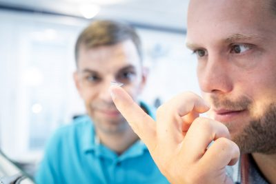Mann betrachtet Kontaktlinse